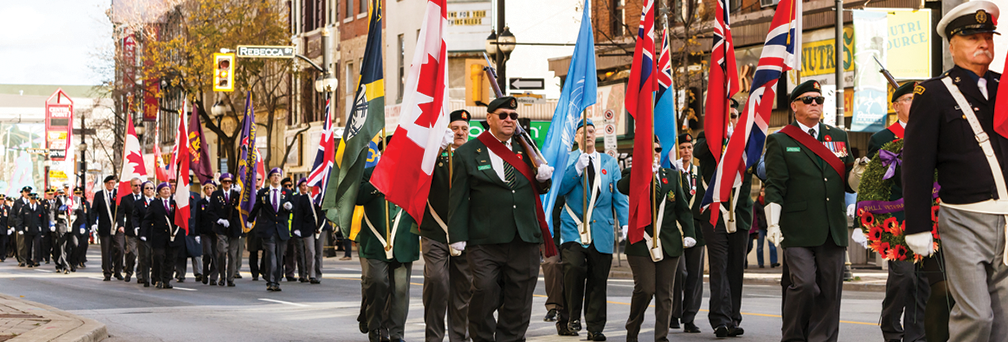 A parade of veterans, city official and service men and women in honour of Remembrance Day