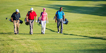 Group of golfers walking up the fairway
