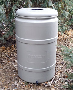Image of a rain barrel outdoors next to trees