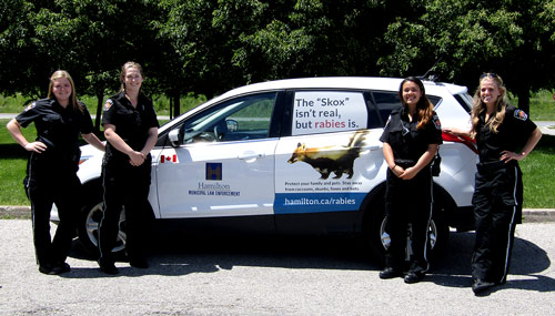 Four young women in Animal Control uniforms pose in front of a City of Hamilton vehicle