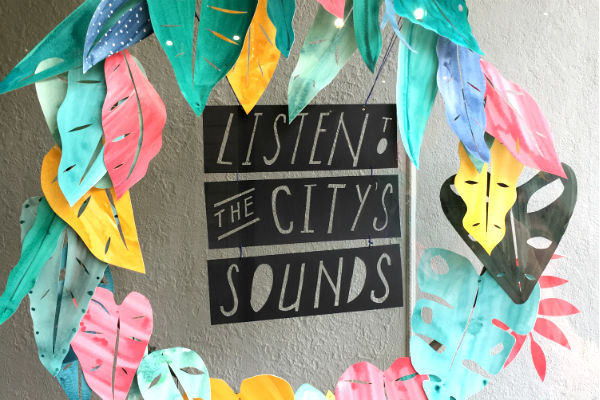 Paper cutouts of leaves in a wreath encircling hand-painted text that reads Listen to the City's Sounds