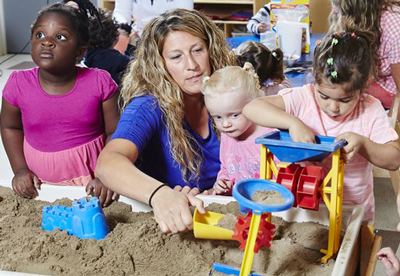 Children with instructor at sandbox