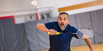 Older man playing badminton in a gym