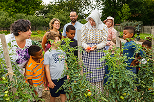 Costumed interpreter guiding a group of visitors on a tour around the historic kitchen garden at Dundurn Castle