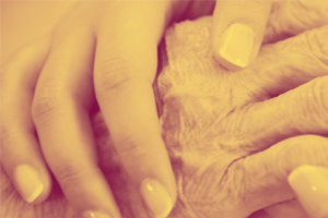 Image of younger person's hand overlaid on an older persons hand in a show of comfort