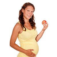 pregnant woman eating holding an appple