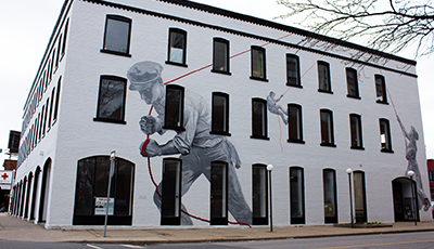 "View of the mural titled ""Raise"" on 2 walls of a heritage building"