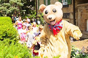 Life size teddy bear leading kids across Whitehern grounds at Teddy Bear Picnic