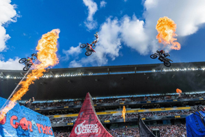 Motorcycles doing stunt jumps with pyrotechnics in the background