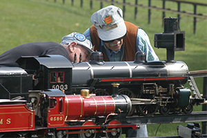 Two men from Golden Horseshoe Live Steamers looking up close at a minature steam locomotive