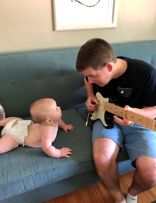 Baby with dad strumming guitar