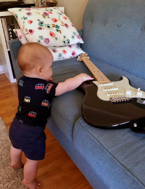 Baby reaching for guitar on a couch