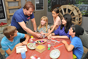 Leader showing a table of kids a crafting project