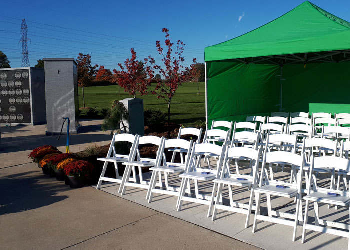 Image of funeral setup with chairs and tent