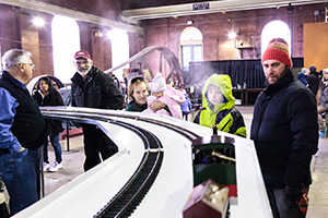 Group of people and children standing beside trains on display at Steam Museum