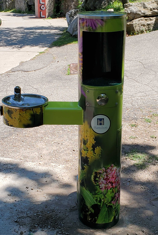 Picture of a drinking fountain wrapped with images of pollinators and flowers