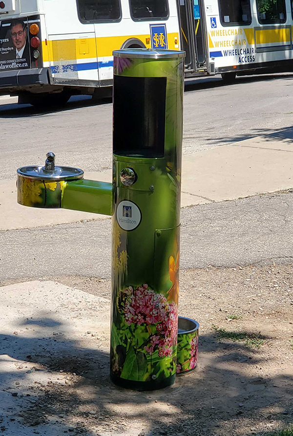 Photo of a drinking water fountain that has been wrapped with images of pollinators and flowers
