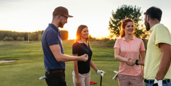 4 people talking on a golf course