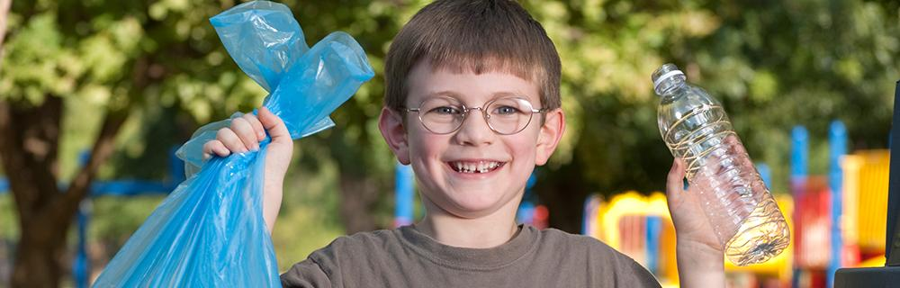 A young boy holding up a garbage bag and a water bottle