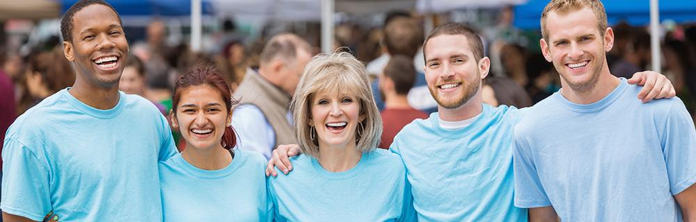 Group of people standing together wearing blue shirts