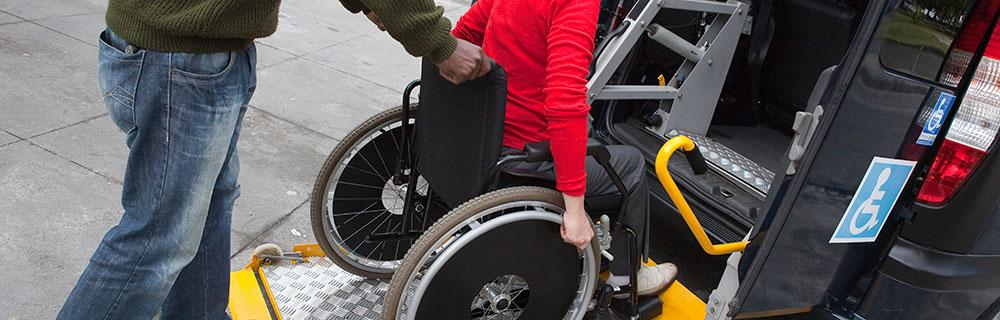 Person in a wheelchair being helped into a vehicle