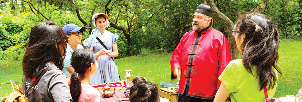 Man and women dressed in historical costumes with a group of people at Sara Calder Day