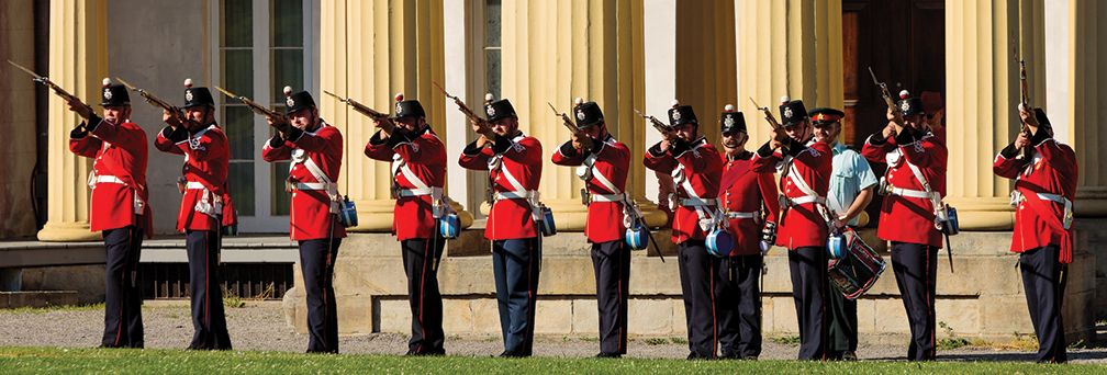 Line of red-coated defenders of Canada West at Ridgeway holidng rifles infront of Dundurn Castle